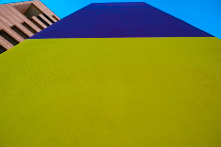 Abstract geometric pattern on concrete wall Architecture Blue Building Building Exterior Built Structure Clear Sky Close-up Copy Space Day Geometric Shape Green Color Low Angle View Multi Colored Nature No People Outdoors Pattern Shape Sky Yellow