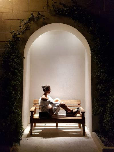 Young woman sitting on bench in arch