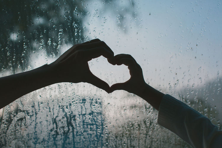Cropped hands gesturing heart shape against wet window
