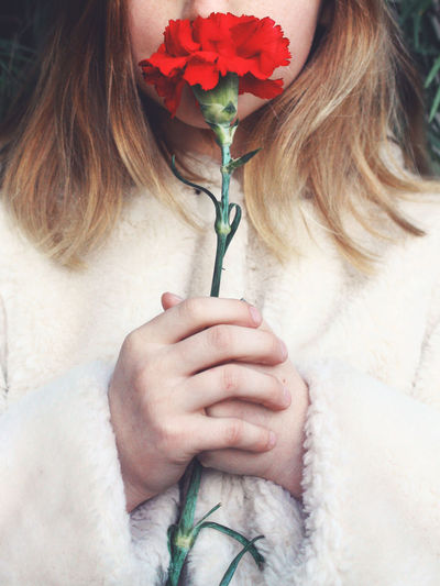 Close-up Cropped Day Flower Flower Head Fragility Growth Holding Holding Flower In Bloom Leisure Activity Lifestyles Nature Part Of Petal Pink Color Plant Red Red Flower Smelling The Roses Softness Stem Touching Unrecognizable Person Youth
