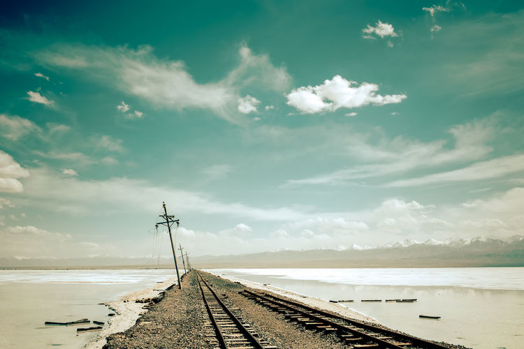 Railway tracks cross over saline desert Cloud - Sky Desert Future Horizon Over Water Lake Landscape Mountain No People Outdoors Path Railway Track Saline Lake Sand Train Track Tranquil Scene Travel Destinations Water Way