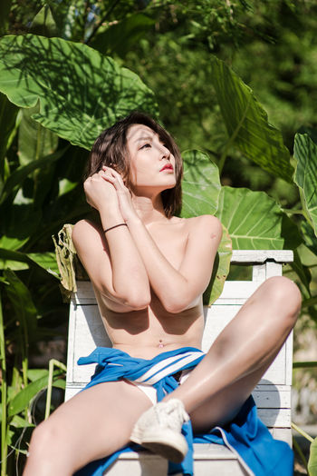 Shirtless Young Woman Sitting Against Plants During Sunny Day