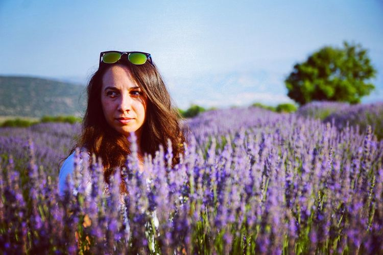 Close-Up Of Woman Looking Away Amidst Lavender Field