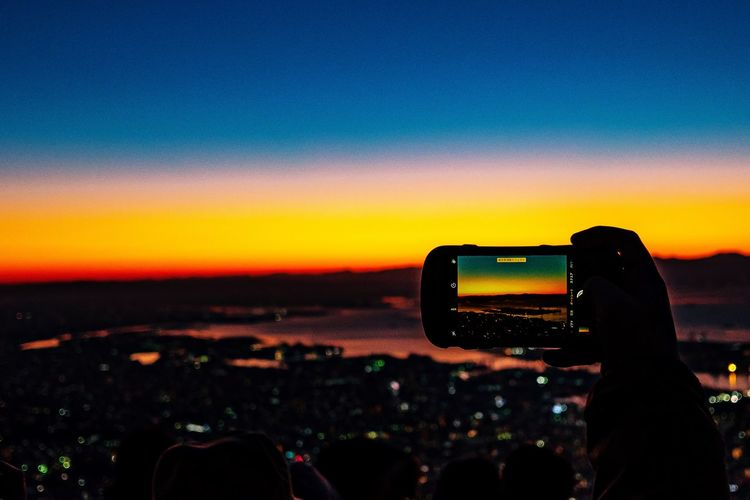Person Photographing Landscape During Sunset