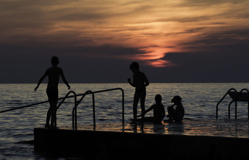 Beach Beauty In Nature Cloud - Sky Group Of People Horizon Over Water Land Leisure Activity Lifestyles Men Nature Orange Color Outdoors Real People Scenics - Nature Sea Silhouette Sky Standing Sunset Water Women