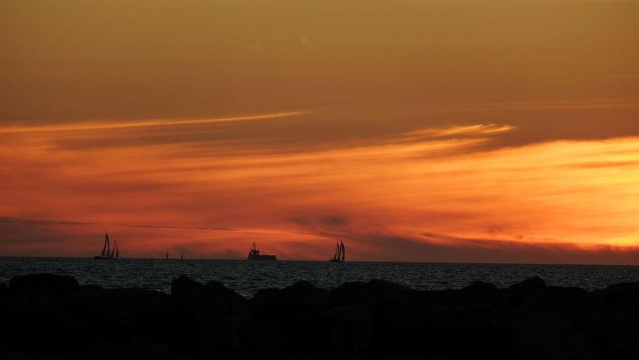 Boats In Calm Sea Against Scenic Sky