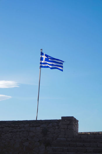 The blue white Greek flag in front of a blue sky ! The Greek Flag White And Blue Flag Blue Sky On Top Of A Rocked Wall Stairs_collection Wall Of Rocks White And Blue Stripes White Cross