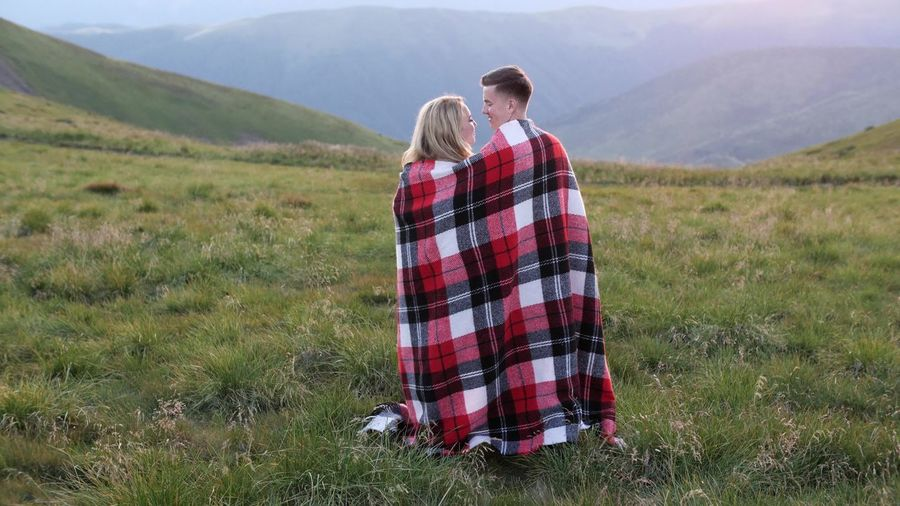 Couple wrapped in blanket standing on field