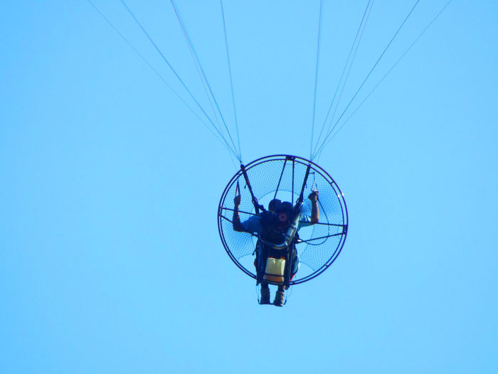 Low Angle View Of Man Paramotoring Against Clear Blue Sky
