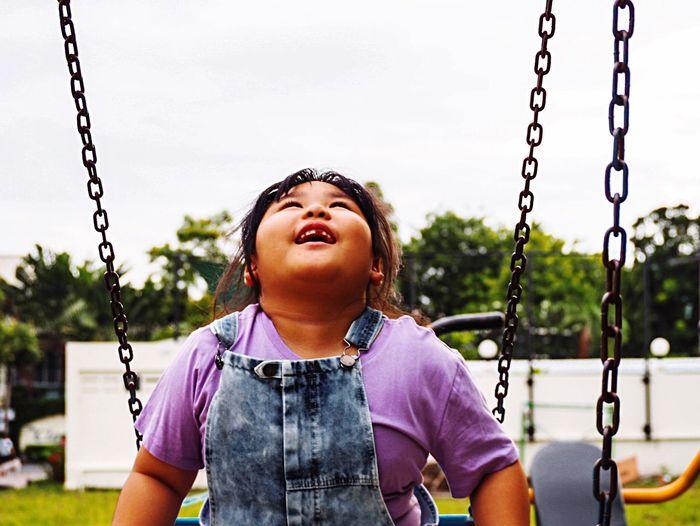 Smiling girl on swing at playground