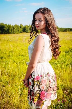 Looking At Camera Young Women Weekend Activities Young Adult Long Hair Grass Three Quarter Length Standing Field Casual Clothing Dress Beauty Medium-length Hair Person Scenics Nature Sky Looking At Camera Day Black Hair Remote Beauty In Nature