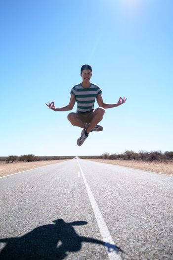 Portrait Of Man Jumping On Road Against Clear Blue Sky
