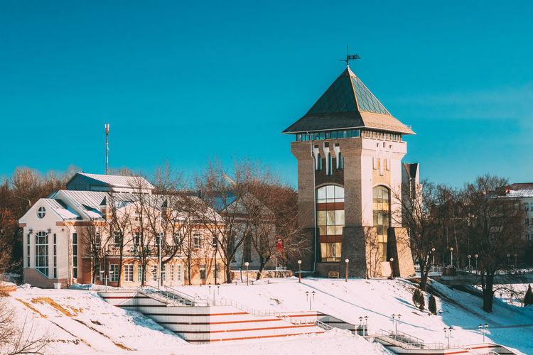 Vitebsk, Belarus. Restored Medieval Tower Duhovskoi Kruglik In Sunny Snowy Winter Day. Vitebsk Snow Architecture Winter Sky Building Tree Tower Sunlight Frozen Blue Belarus Restored Medieval Duhovskoi Kruglik Sunny Snowy Day Travel