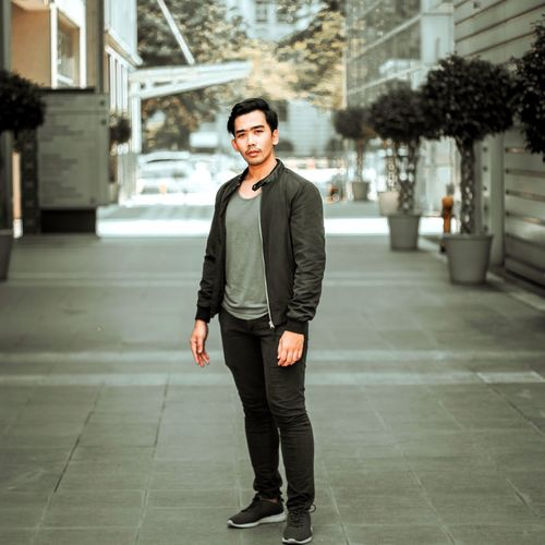Portrait of handsome young man standing in city