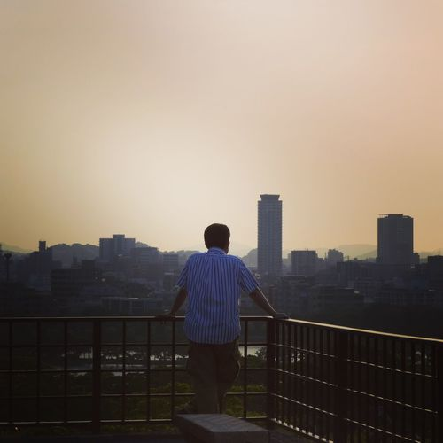 Contemplating Man Fukuoka Japanese Culture Japan Contemplating Rear View Architecture Cityscape Building Exterior Railing Built Structure One Man Only Standing Sunset Full Length Urban Skyline Real People