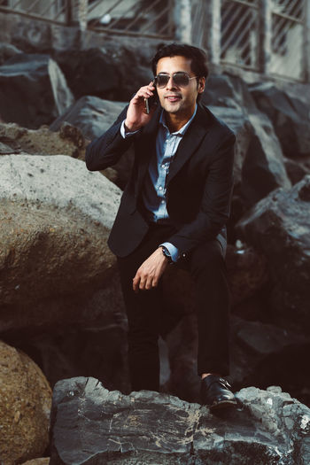 Young Businessman Talking On Mobile Phone While Standing Amidst Rocks