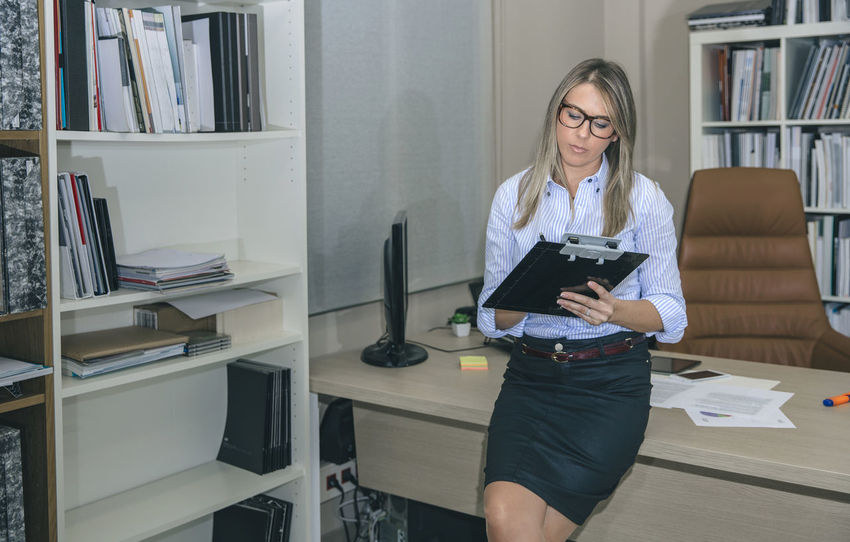 Beautiful young woman writing notes at her workplace Business Busy Company Female Power Glasses Horizontal Leader Woman Working Writing Beauty Business Finance And Industry Businesswoman Caucasian Chief Executive  Female Headquarters Job Notebook One Person Portrait Professional Real People Sucess