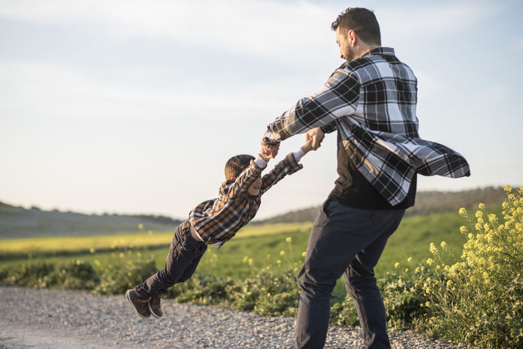 Father playing with daughter on field