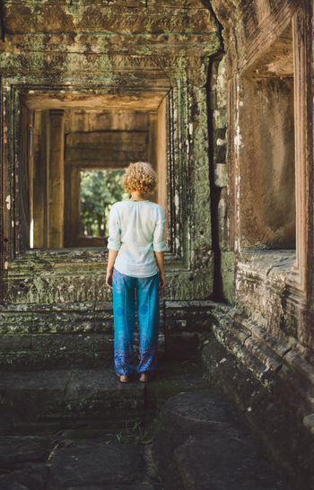 Rear View Of Mid Adult Woman Standing Outside Ankor Wat Temple