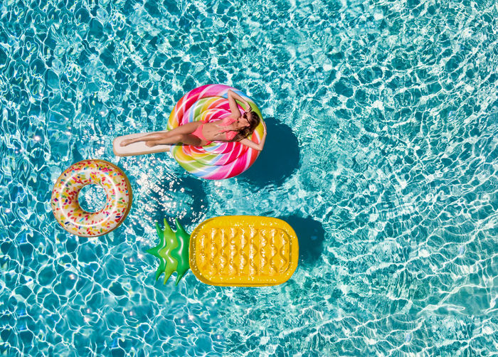 High angle view of woman floating on inflatable lollipop in swimming pool