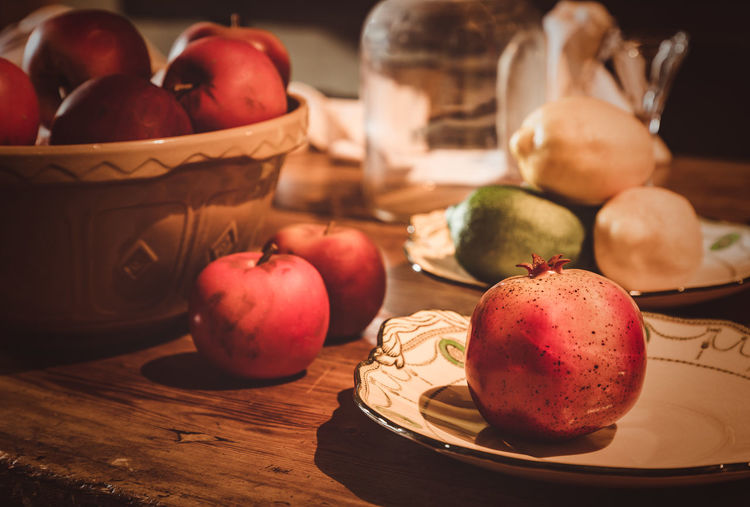 Old fashioned kitchen table with pomegranates and bowls of apples. Food And Drink Food Healthy Eating Freshness Fruit Wellbeing Still Life Table Container Apple - Fruit No People Indoors  Close-up Vegetable Basket Red Focus On Foreground Pomegranate Apple Christmas Xmas Apples Apple Kitchen Table Old Fashioned
