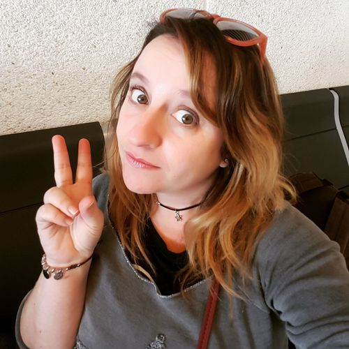 Portrait of woman showing peace sign against wall