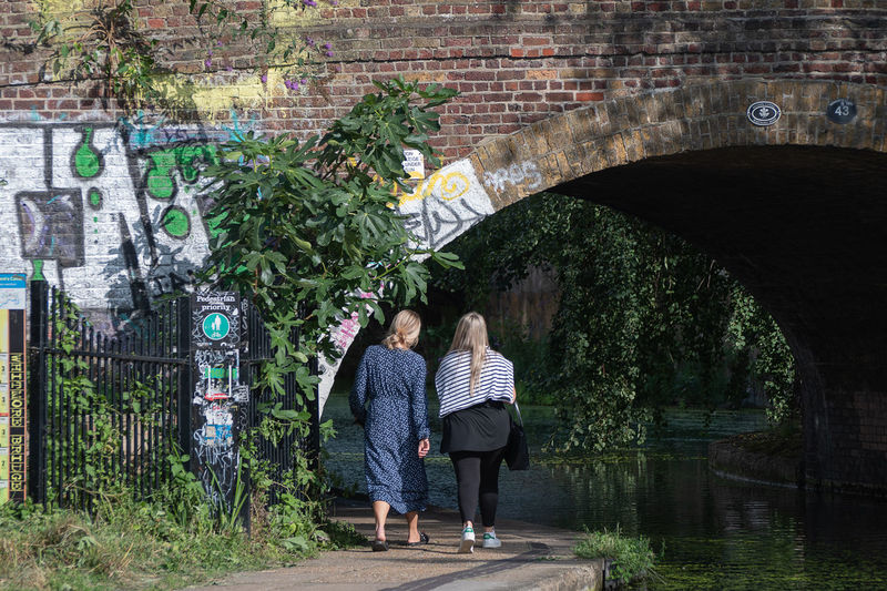Rear view of women standing on bridge