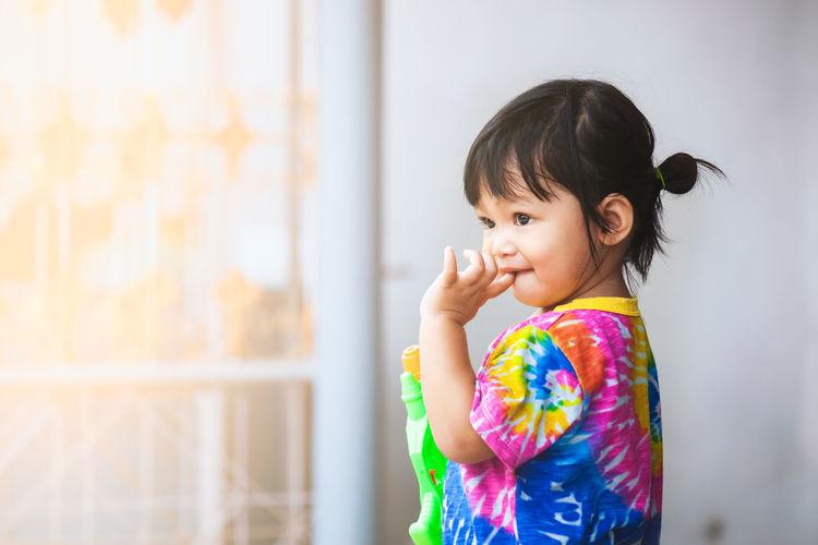 Cute baby girl holding squirt gun