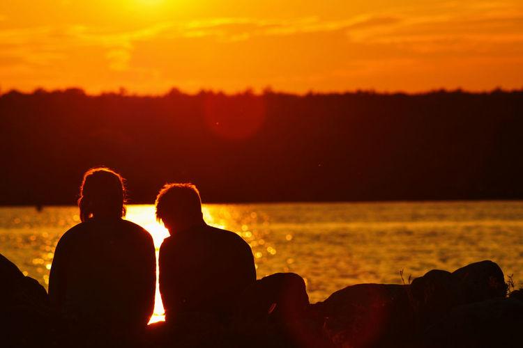 Silhouette friends sitting by sea against orange sky