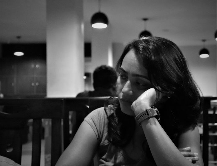 Monochrome portrait of woman absorbed in her thoughts in a restaurant