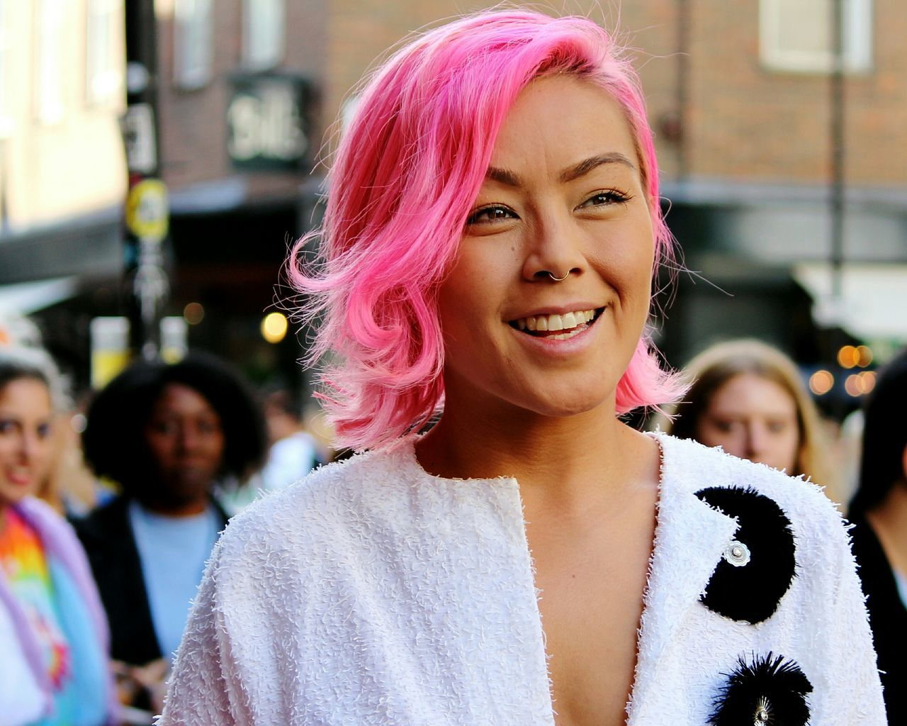 PORTRAIT OF HAPPY YOUNG WOMAN WITH PINK HAIR