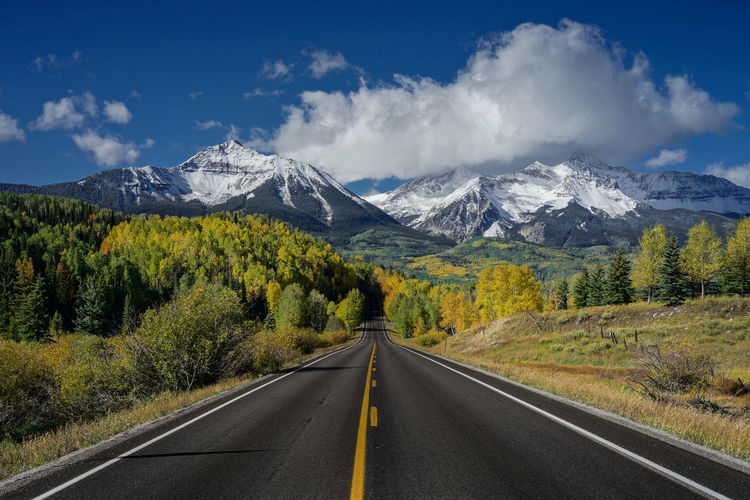 Road to mountain in autumn with aspen yellow leafs