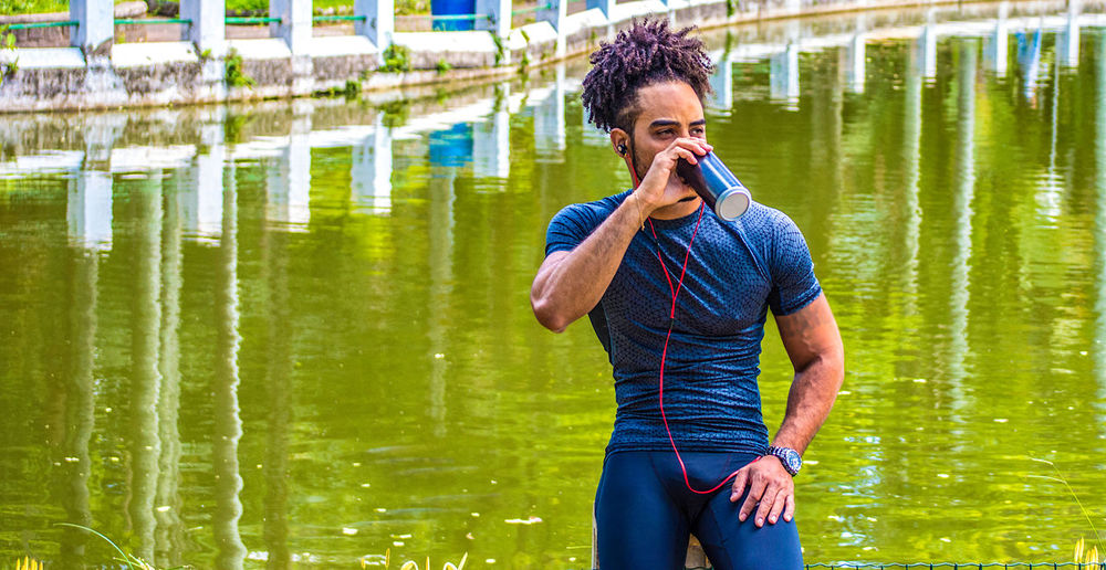 Young man drinking water while listening music against lake
