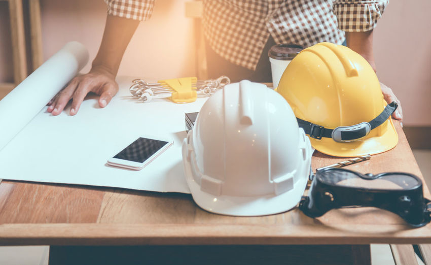 Teams of engineers architect meeting design project discussion work concept at construction site in the office with business concept. Architecture Business Construction TEAMS Adult Concept Engineers Finger Hand Headwear Helmet Holding Lifestyles Men Midsection Occupation Table Working Yellow