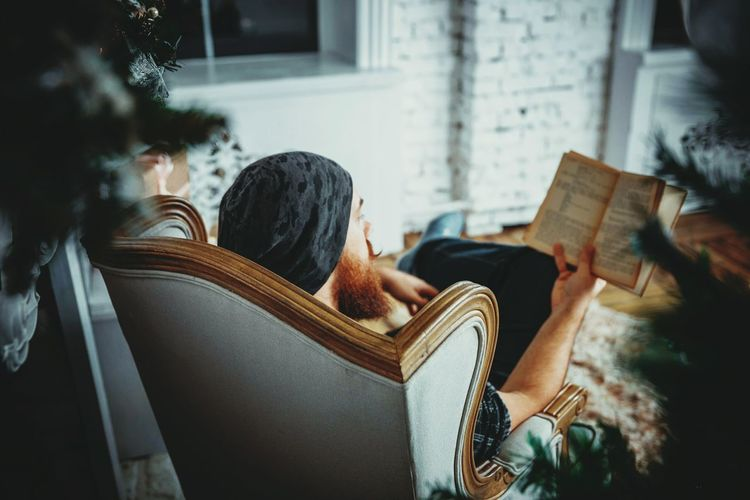 High angle view of man reading book while sitting on arm chair