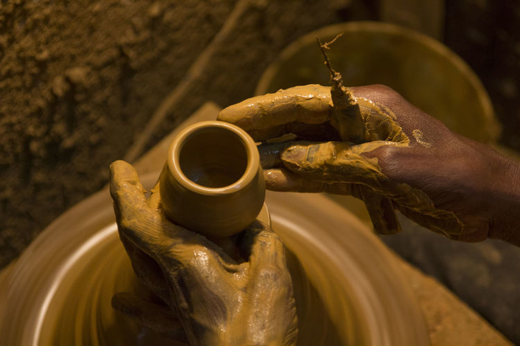 A skilled potter making cups from clay EyeEmNewHere Clay Close-up Day Earthenware Focus On Foreground Holding Human Body Part Human Finger Human Hand Indoors  Making Men Occupation One Person People Real People Skill  Working Workshop