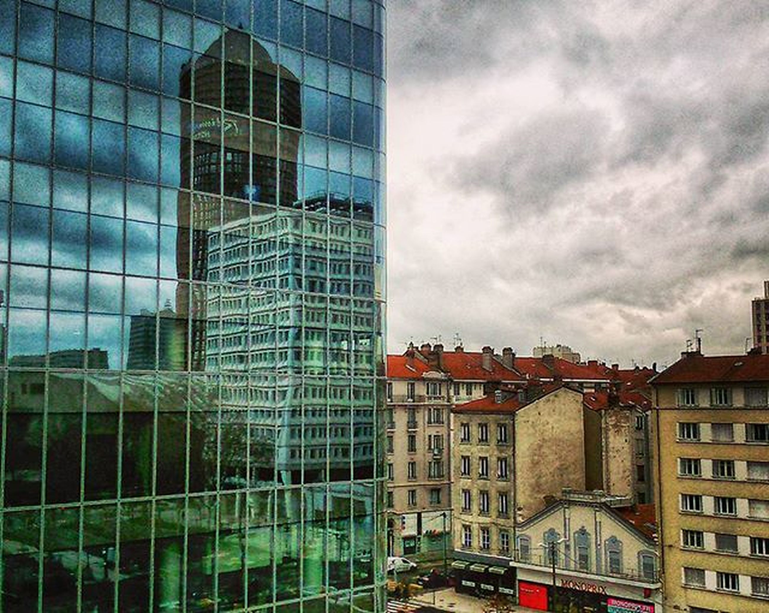 building exterior, architecture, built structure, city, sky, modern, office building, cloud - sky, building, glass - material, skyscraper, cloudy, window, low angle view, city life, tall - high, residential building, car, cloud, day