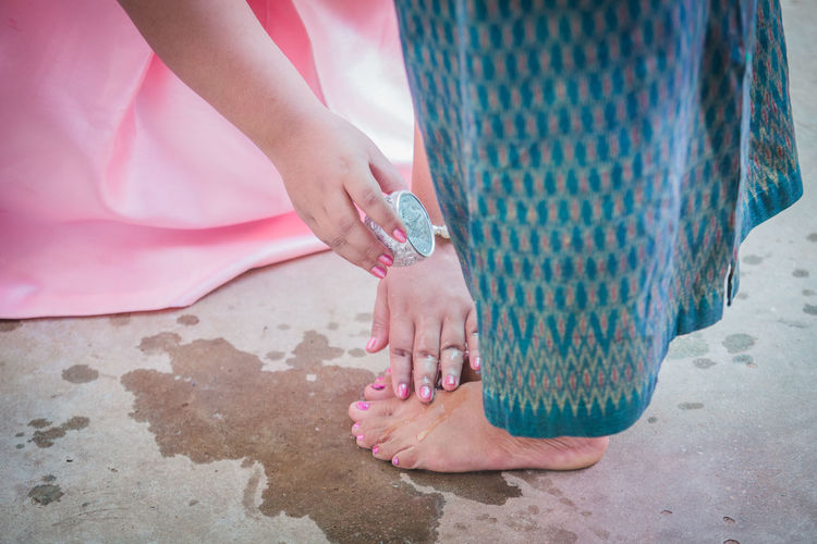 Bride pouring water on legs of mother during wedding