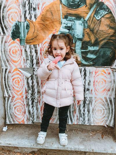 Full length portrait of cute girl standing against graffiti