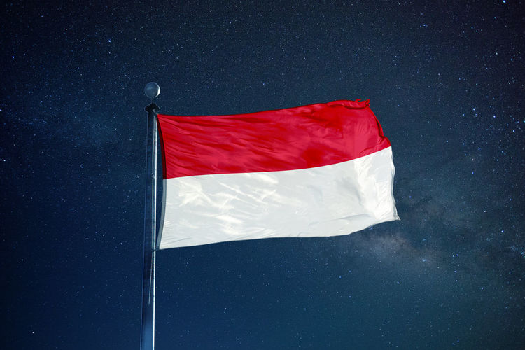 Low angle view of indonesian flag against star field sky