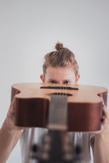 Portrait of man playing guitar against white background