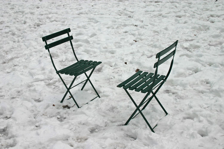 High angle view of empty chairs on snow