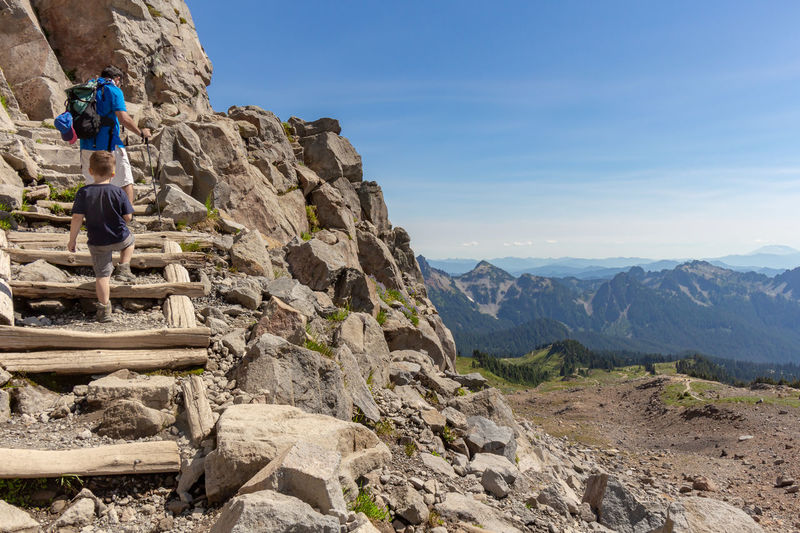 Rear view of father and son climbing steps on mountain