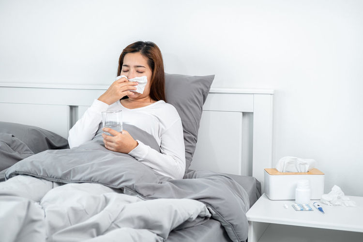 Midsection of woman drinking coffee while sitting on bed