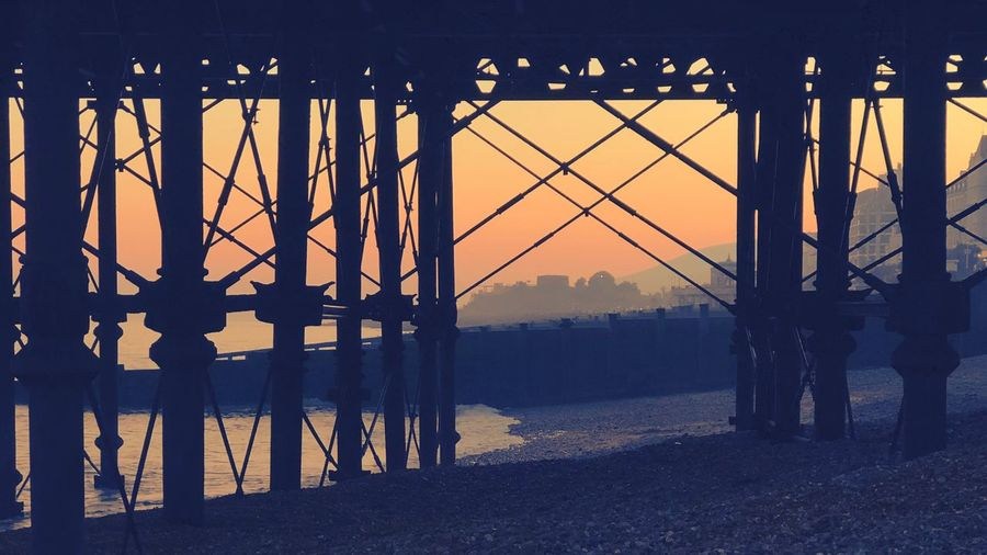 Pier structure Seaside Tides Sussex Eastbourne Beach Sunset Architecture Built Structure Water Sky Bridge Nature No People Metal Bridge - Man Made Structure Silhouette Sunlight Orange Color Sea