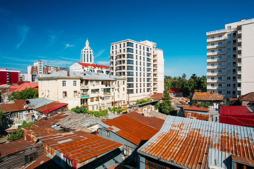 Modern Houses Rise Above The Old Rusty Roofs In Batumi, Adjara Georgia. Urban Architectural Cityscape Of Georgian Resort Town Of Batumi. Batumi Colour Your Horizn Georgia Modern Travel Adjara Architecture Blue Building Exterior City Cityscape Day House Modern Love Outdoors Roof Sky Tourism Town Urban