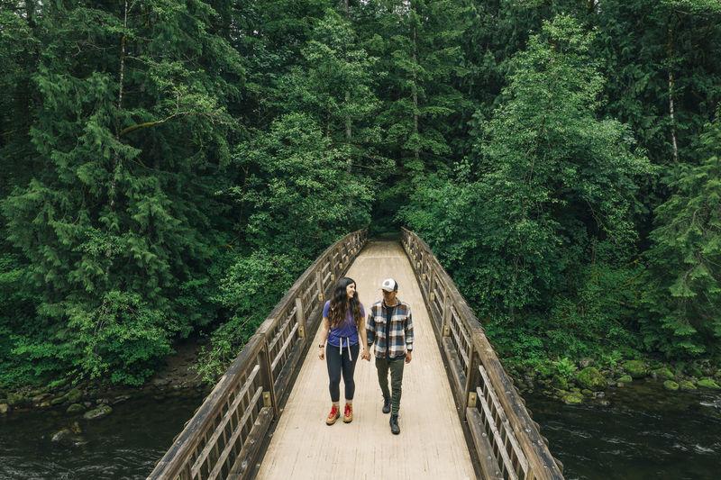 People standing on footbridge in forest