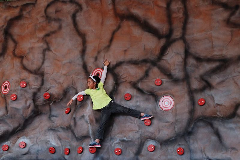 Full Length Of Girl Hanging On Climbing Wall
