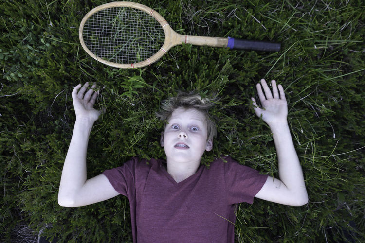 Boy lying on field with badminton racket