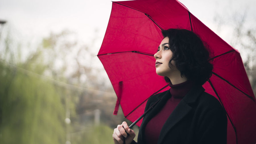 Portrait of woman with red umbrella standing in rain
